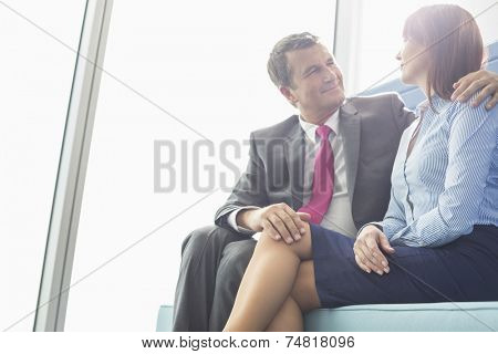 Mature businessman flirting with female colleague in office