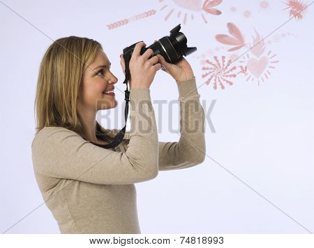 Side view of young woman photographing various patters over white background