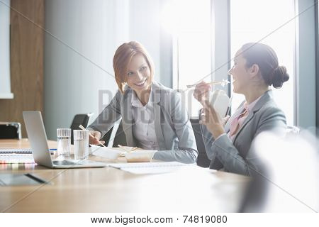 Smiling young businesswomen having lunch at table in office