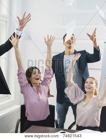 Businesspeople throwing papers in the air at office