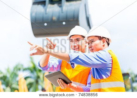 Asian engineer controlling construction machinery of construction site or mining company