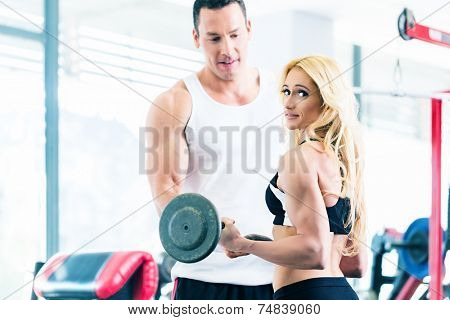Woman in gym training for body building competition with barbell assisted by personal fitness trainer