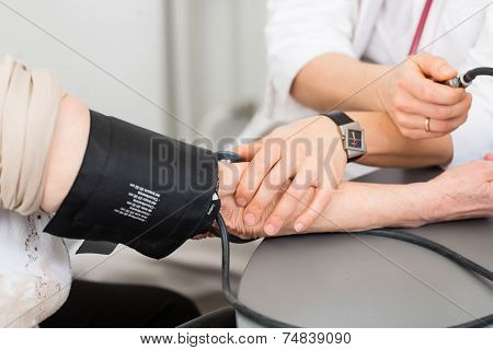 Young female doctor measuring blood pressure of senior patient in surgery consultation hour