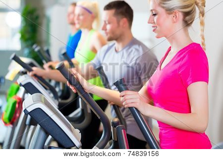 Group of fitness people in sport gym on treadmill