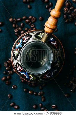 Decorative vintage Arabic Cezve for making Turkish coffee viewed above  surrounded by whole roasted coffee beans below