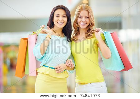 Portrait of two happy shoppers with paperbags looking at camera