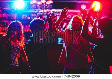 Ecstatic friends with raised arms dancing in nightclub