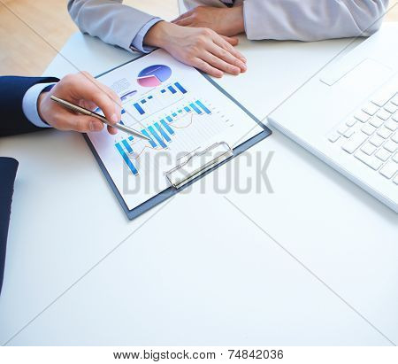 Close-up of male hand pointing at business document while explaining it to businesswoman