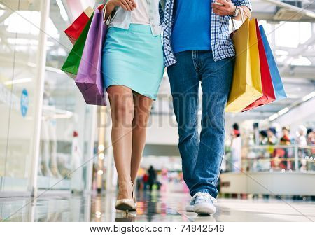 Legs of young couple with paperbags going in the mall