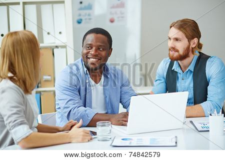 Two male employees listening to explanations of their colleague at business meeting