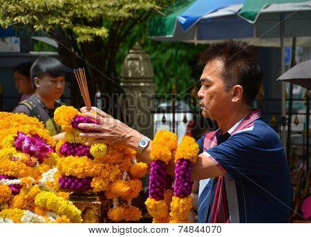 Man Makes Offering At Erawan Hindu Shrine In  Bangkok.