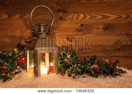 Christmas candle lantern in snow surrounded by holly with red berries against a rustic wooden background.