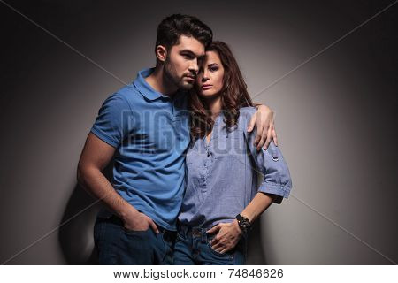 Portrait of a young fashion couple posing with their hands in pockets.