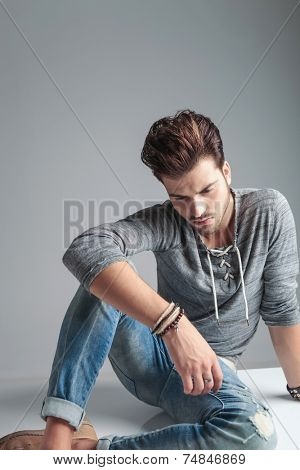 Picture of a young fashion man looking down while relaxing on the floor holding his arm on his knee.