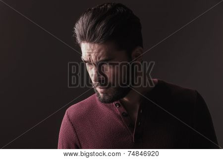 Close up picture of a casual young man looking angry away from the camera. On dark studio background.