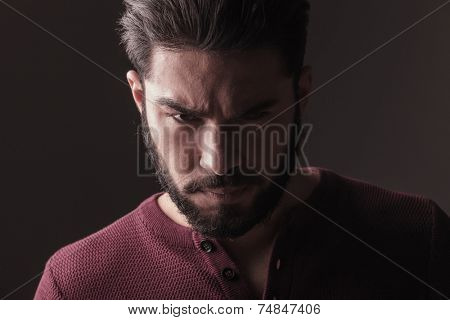 Close up picture of a handsome casual man looking at the camera with a angry look on his face.