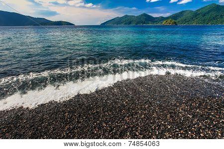 Beautiful Crystal Clear Sea With Black Pebble Beach