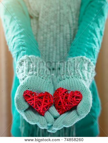 Female hands in light teal knitted mittens with entwined red heart Love and St. Valentines Day concept.