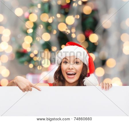 christmas, x-mas, people, advertisement and sale concept - happy woman in santa helper hat with blank white board over tree lights background