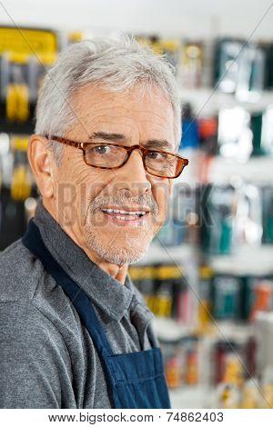 Closeup portrait of senior salesman smiling in hardware store