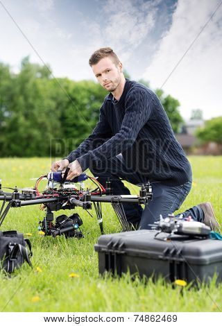 Portrait of confident young technician assembling UAV drone in park