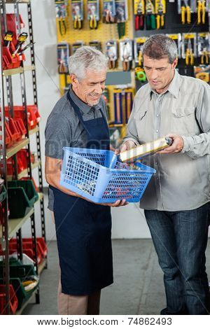 Senior salesman assisting male customer in buying product at hardware store