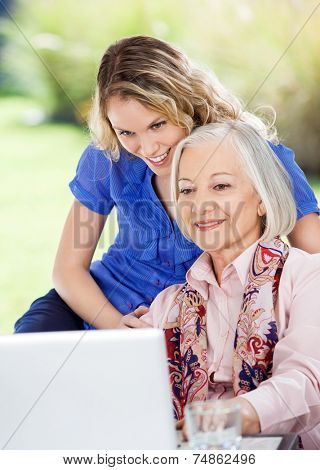 Smiling senior woman and granddaughter using laptop at nursing home porch