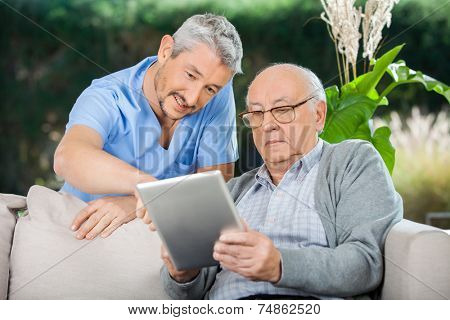 Male caretaker assisting senior man in using digital tablet at nursing home porch