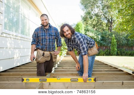Portrait of happy construction worker checking level of wood with spirit level while standing with coworker at it
