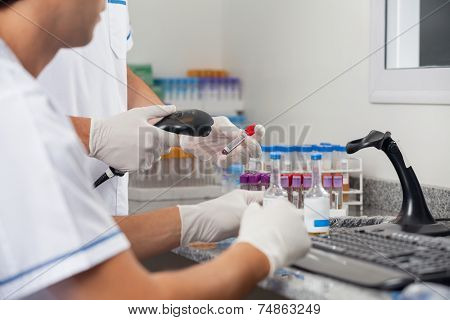 Cropped image of male technicians scanning specimens with barcode reader in lab