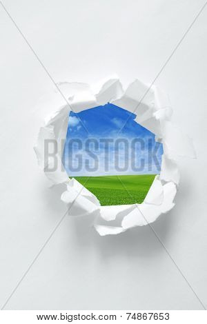 Paper hole with nature background. Focus on curled edges of paper