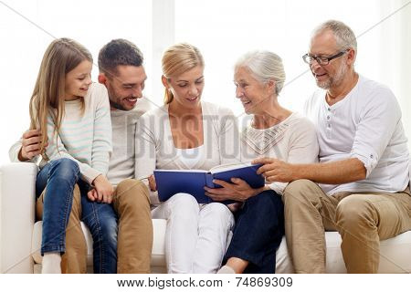 family, happiness, generation and people concept - happy family with book or photo album sitting on couch at home