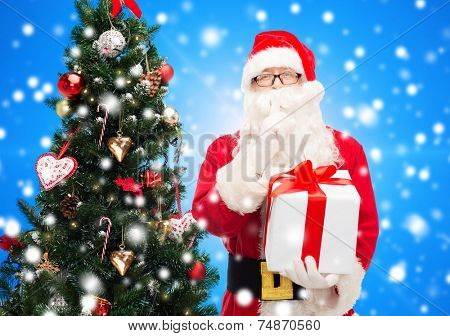 christmas, holidays and people concept - man in costume of santa claus with gift box and tree making hush gesture over blue lights background over blue snowy background