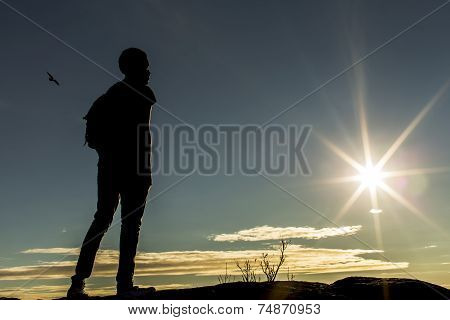 Silhouette man on top of a mountain looking at the sun