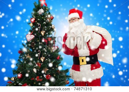 christmas, holidays and people concept - man in costume of santa claus with bag and christmas tree making hush gesture over blue snowy background