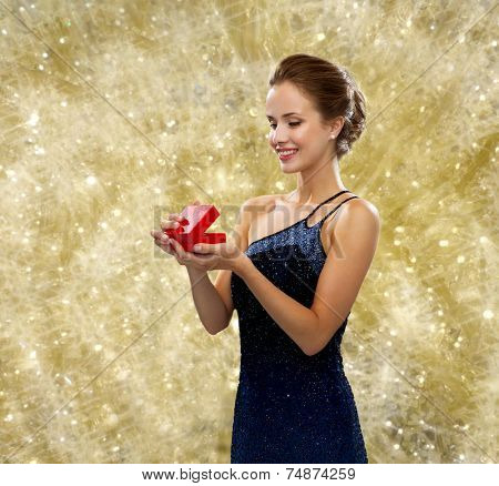 winter holidays, christmas, presents, luxury and people concept - smiling woman in dress holding red gift box over yellow lights background