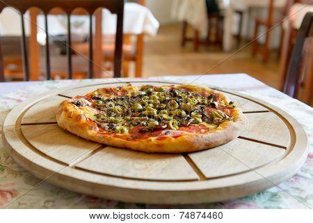 Fresh original Italian pizza on a wooden board in Italian pizzeria