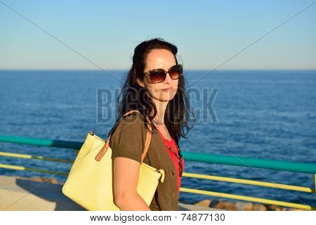Happy young woman walking on the beach promenade