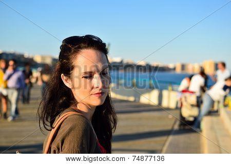 Happy woman walking on the beach promenade