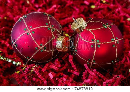 Christmas decorations lying on a bed of crinkle cut shredded paper.
