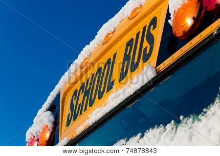 The front of a school bus after a fresh winter snowfall.