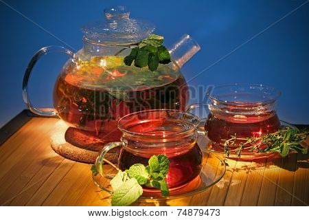 Hot Tea With Curative Herbs In Teapot And Cups