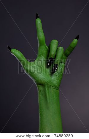 Green hand with black nails showing heavy metal gesture, studio shot on black background