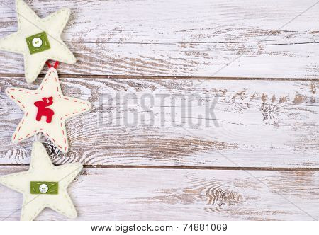 Christmas decoration. Felt stars on white, wooden background with copy space