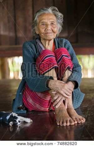 BAM MUANG PAM, THAILAND, NOVEMBER 22 : An elderly Karen tribe woman, Thai ethnicity, is posing in her wooden house, her cat lying beside, village of Bam Muang Pam, north Thailand on November 22, 2012