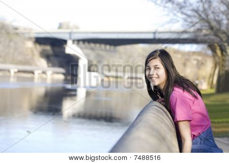Girl Standing On River Bank