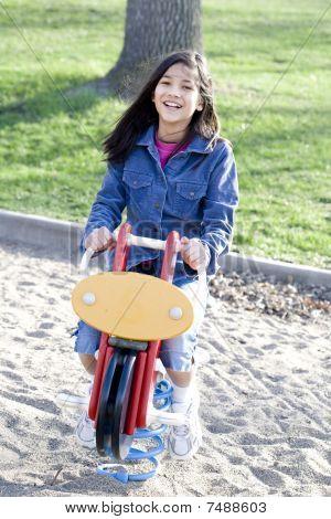 Girl Playing On Playground Rocking Horse