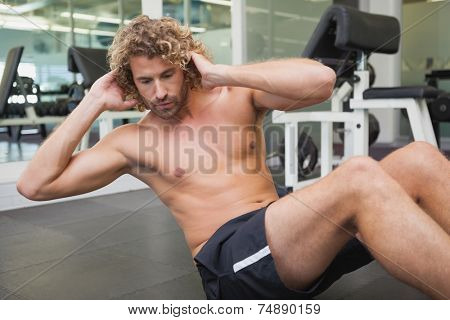 Side view of handsome young man doing abdominal crunches in gym