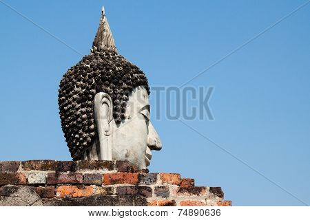 Buddha head behind the wall with clear blue sky