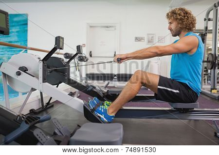 Side view of a handsome young man using resistance band in gym